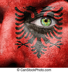 Flag painted on face with green eye to show Albania support