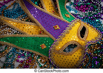 A yellow Mardi Gras mask and beads - A yellow Mardi Gras...