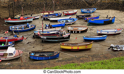 Low tide in the harbor with fishing trawlers