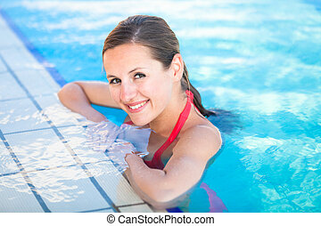 Portrait of a young woman relaxing in a swimming pool...