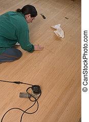 woman refinishing oak floors, applying filler
