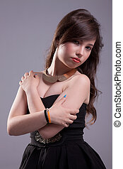 beautiful young woman with elegant black dress,to hold up. studio shot
