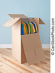 Wardrobe box with colorful clothing, ready for moving -...