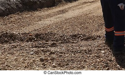 Construction site - Roadworks, manual worker throw gravel...