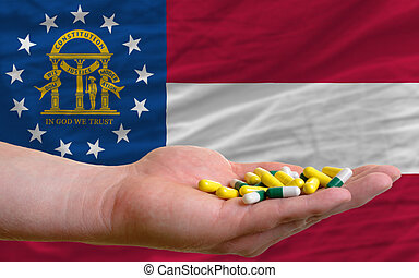 holding pills in hand in front of georgia us state flag