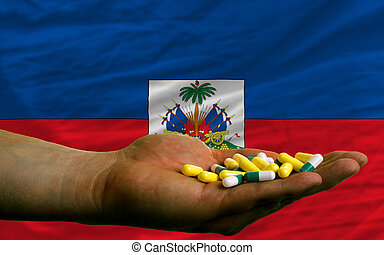 holding pills in hand in front of haiti national flag