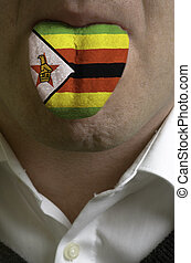 man wit open mouth spreading tongue colored in zimbabwe flag...