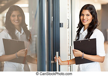 beautiful young indian white collar worker opening office...