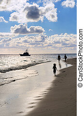 Family walking on a beach - Family taking a walk on a sandy...