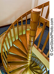 Spiral wooden staircase with varnished balusters between the...