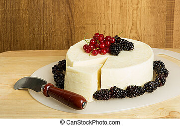 Round of white cheese decorated with currants and berries