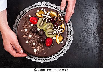 Confectioner and his cake on steel background
