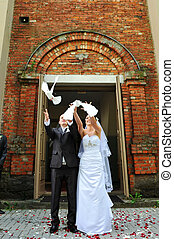 newlyweds with doves - newlyweds releasing white doves....