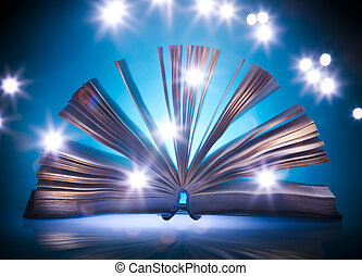 Open old book, mystical blue light at background, light...