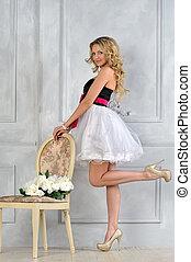 Beautiful blonde woman in fancy dress in luxury interior.