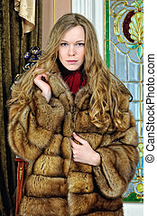 beautiful woman in fur coat in the luxurious antique...