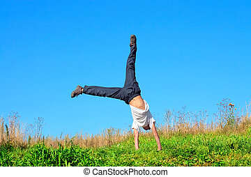 teenager in the field - somersault on the summer meadow