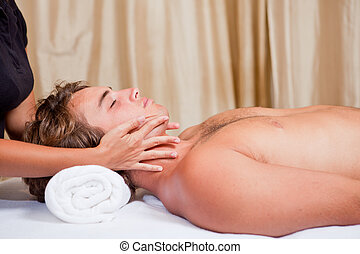 man at massage spa - man getting neck face and head massage...