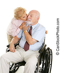 Devoted Senior Couple - Senior man in wheelchair receiving a...