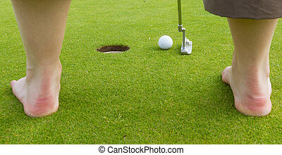 Golf player hitting the ball close-up on whole (barefoot)