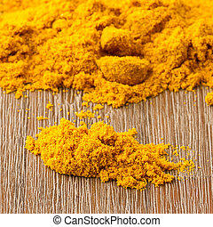 Heap of turmeric on isolated wood background