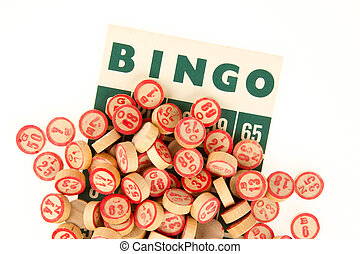 Wooden numbers used for bingo, on top of a bingo card