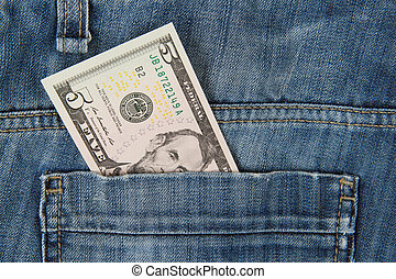 Macro shot of trendy jeans with american 5 dollar bill on...