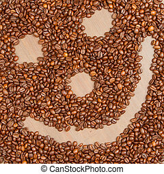 Coffee grains arranged in smiley. Isolated on wooden...