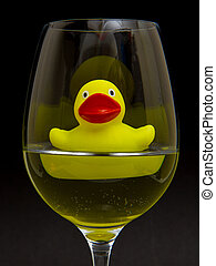 Yellow rubber duck in a wineglass with water (black...