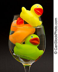 Yellow, orange and green rubber duck in a wineglass with...
