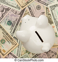 Piggy bank on dollar bills, focus on the pig