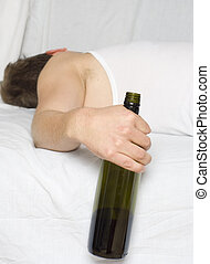 Man in bed with a wine bottle