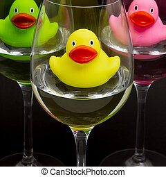 Green, yellow and pink rubber ducks in wineglasses, dark...