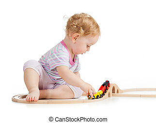 serious child is playing with wooden train isolated on white
