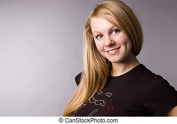A smiling blonde on a grey background in studio.