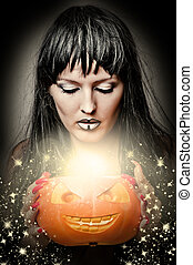 woman witch making magic to pumpkin - Sexy brunette woman...