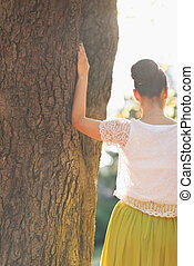 Young woman lean against tree Rear view