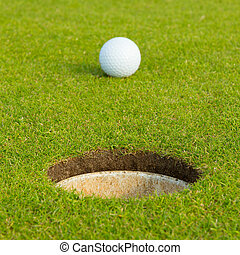 Golf ball in front of the hole, focus on the hole - Golf...