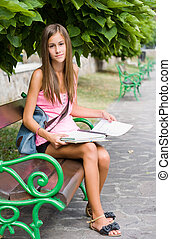 Beautiful young student girl studying outdoors - Portrait of...