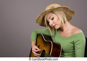 Blonde Strumming Guitar - A blonde woman in a straw hat...