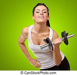 Young woman holding dumbells on green background