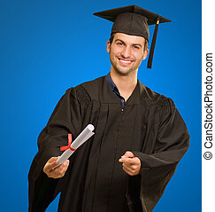 Young Man In Graduation Gown Holding Certificate On Blue...
