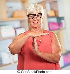 Portrait Of A Senior Woman Showing Time Out Signal, Indoor