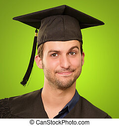 Young Man In Graduation Gown On Green Background