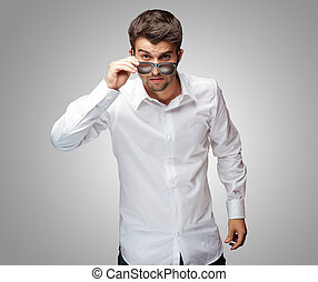 Portrait Of Young Man Giving Look While Holding Glasses On...