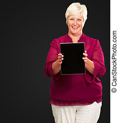 Senior Woman Holding A Touchpad On A Black Background