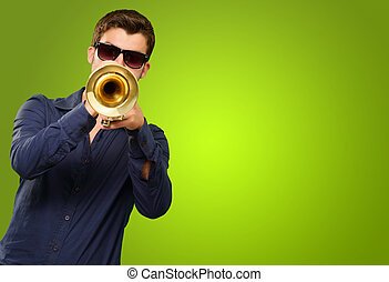 A Young Man Blowing A Trumpet On Green Background