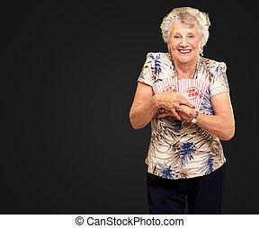 Portrait Of A Senior Woman Holding Popcorn Box