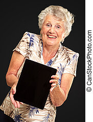 Portrait Of A Senior Woman Holding A Digital Tablet On Black...