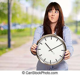 A Young Girl Holding A Clock And Making Face, Outdoor